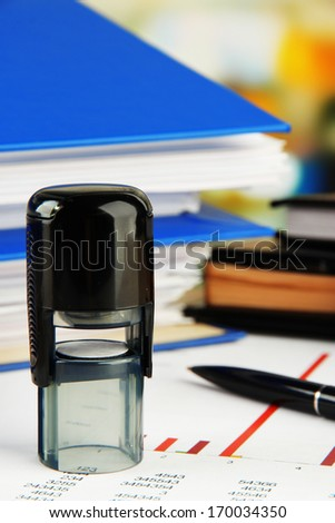 Stamp with notepads and papers on table - stock photo