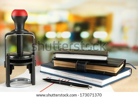 Stamp with notepads and papers on table on bright background - stock photo