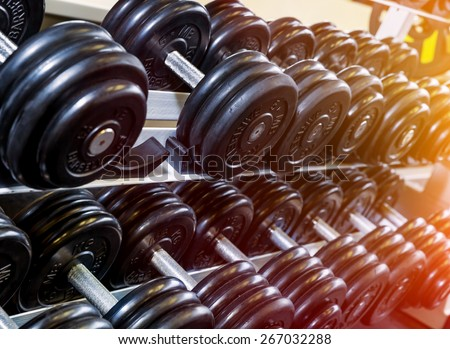 Stand holder for dumbbells in the gym. Soft focus  - stock photo