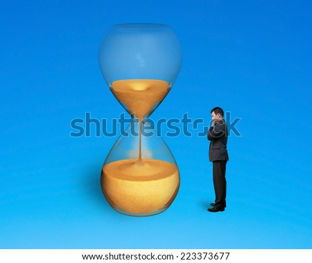 stand man watch hourglass isolated on blue