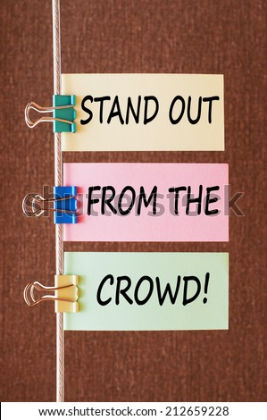 Stand out from the crowd concept. Business message text wording on colorful note papers on a rope - stock photo
