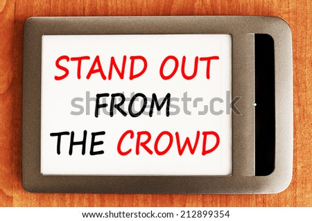 Stand out from the crowd concept. Business message text wording on e-book - stock photo