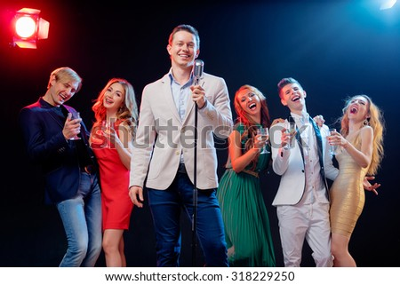Stand-up comedy and party. Showman with microphone. Group of cheerful friends toasting with wineglasses among confetti. - stock photo