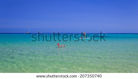 Stand up paddle board man paddleboarding on Mediterranean Sea with a sailing boat in the background