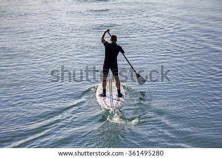 Stand up paddle board man paddleboarding on tranquil lake - stock photo