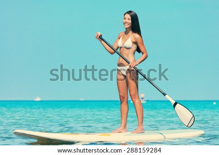 Stand up paddle board woman paddleboarding on SUP on Hawaii standing happy on paddleboard on in water. Young mixed race Asian Caucasian female model on Hawaiian beach on summer holidays vacation. - stock photo