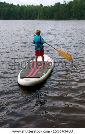 Stand Up Paddle Board young boy paddles for the first time on the calm lake - stock photo