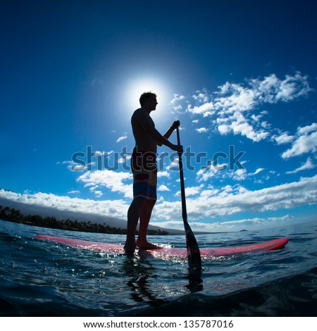 Stand up paddle boarder exercising in the ocean