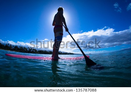 Stand up paddle boarder exercising in the ocean - stock photo