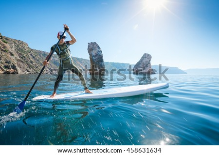 Stand up paddle boarding. Young man floating on a SUP board. The adventure of the sea with blue water on a surfing. - stock photo