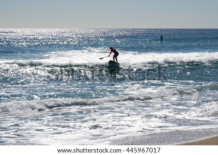 Stand up paddle surfing or standup paddle boarding SUP in the mediterranean sea