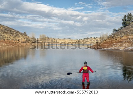stand up paddler dressed in a drysuit  for cold season paddling on a shore of mountain lake in Colorado (Horsetooth Reservoir near Fort Collins)