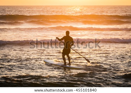 Stand up paddler silhouette at sunset. Concept about sport, surf, vacations and people.
