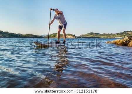 stand up paddling workout on Horsetooth Reservoir at foothills of Rocky Mountains near Fort Collins, Colorado, summer scenery - stock photo