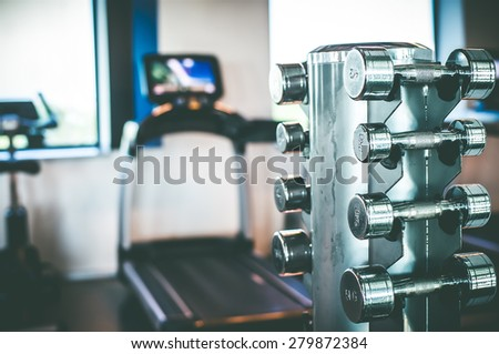 Stand with a dumbbell in the gym - stock photo