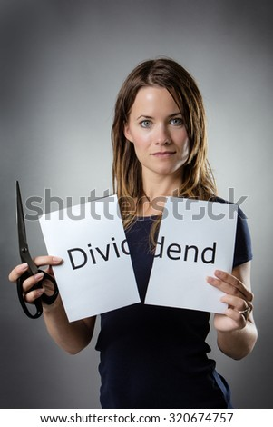 stand woman cutting paper in half with the word dividend written on the paper