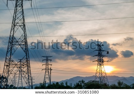 standard overhead power line transmission tower at sunset.