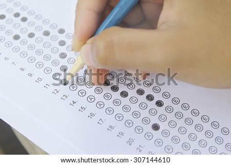 Standardized test form with answers bubbled in and a pencil, focus on anser sheet - stock photo