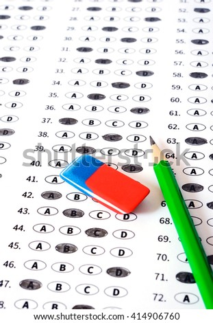 Standardized test form with answers bubbled in and a pencil, focus on answer sheet - stock photo