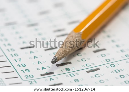 Standardized test form with answers bubbled in and a pencil resting on the paper with a shallow depth of field  - stock photo