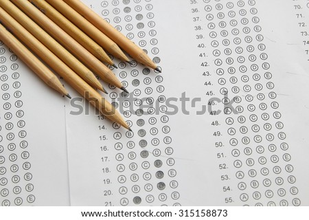 Standardized test form with answers filled in and a pencil, focus on answer sheet