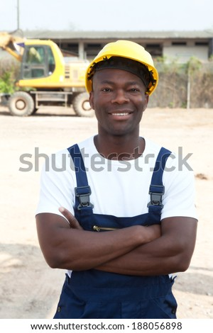 Standing african worker with crossed arms at construction site   - stock photo