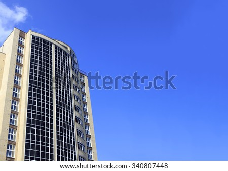 standing alone high-rise building. large office building against the blue sky, copy space for your text - stock photo