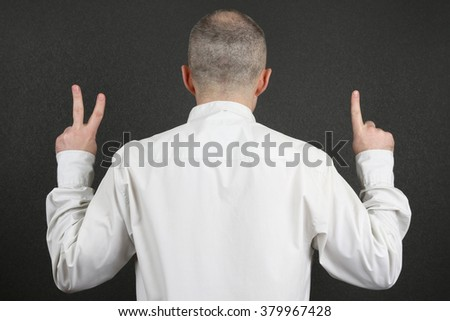 standing back, the man hands shows the signs of 2 and 1  - stock photo
