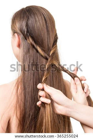 Standing behind the woman doing her hair close up on white background