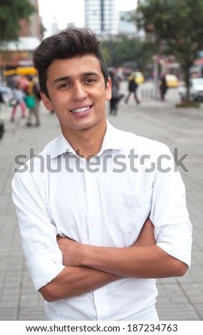Standing brazilian student with crossed arms in the city