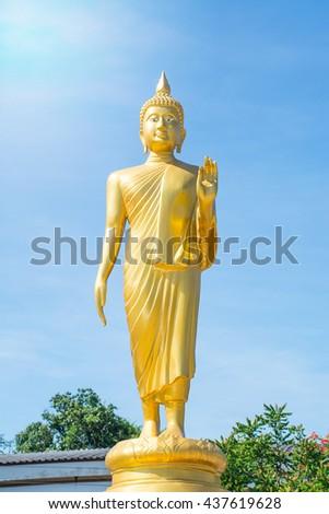 Standing Buddha status on the blue sky. - stock photo