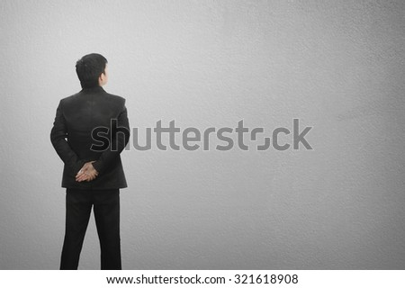 Standing business man and blank wall for text and background.Copy space. - stock photo