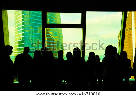 Standing business people silhouette. crowd persons inside modern building with wide blue enter hall window in Moscow city building skyscraper