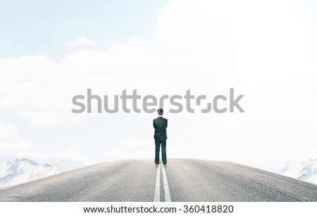 standing businessman and looking on road - stock photo