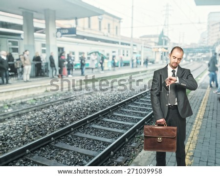 standing businessman at train station - stock photo