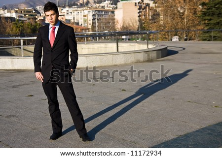 Standing businessman posing on city background - stock photo