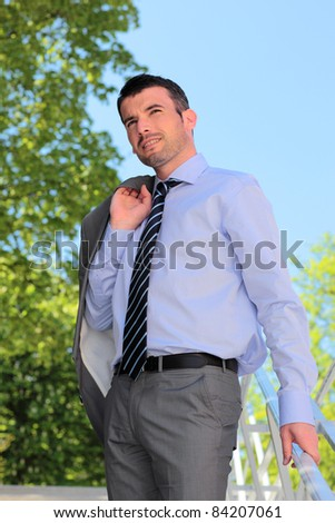 standing businessman waiting outdoor in summer on stairs - stock photo
