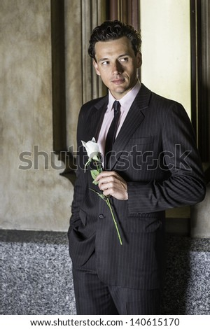 Standing by a window and dressing formally , a young handsome guy is holding a white rose and waiting for you.