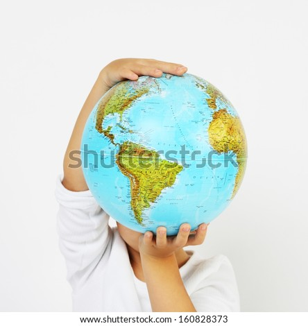 Standing child boy holding a globe in hands in front of his head on white background