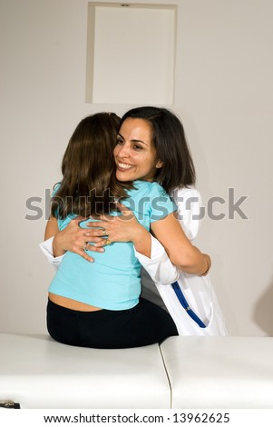 Standing female nurse, in white lab coat, hugging a little girl sitting on bed in a medical office. - stock photo