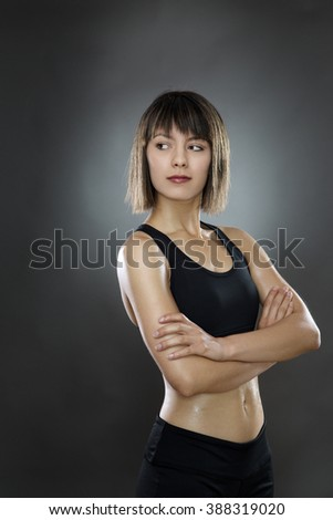 standing fitness woman shot in the studio on a gray background low key lighting - stock photo