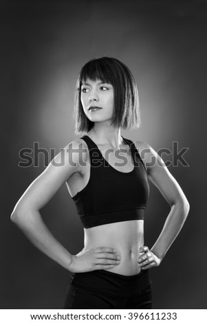standing fitness woman shot in the studio on a gray background low key lighting