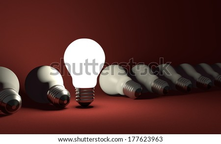 Standing glowing light bulb in row of lying switched off ones on dark red textured background
