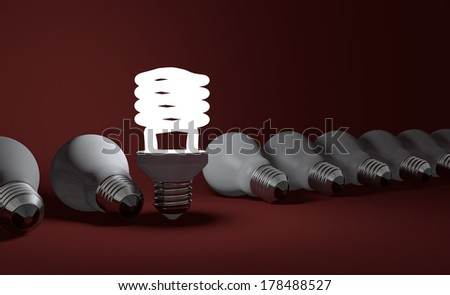 Standing glowing spiral light bulb in row of lying dead incandescent ones on dark red textured background
