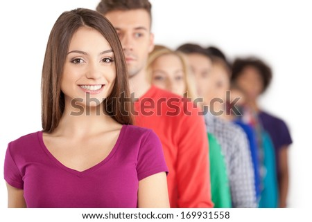 Standing in a row. Young people standing in a row while beautiful young woman standing in front of them and smiling - stock photo