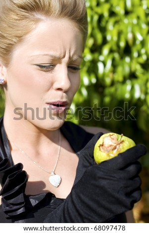 Standing In The Garden Of Eden Eve Takes A Bite Out Of A Chosen Forbidden Fruit Only To Discover With A Look Of Disgust That This Lovely Green Apple Is Rotten To Its Core - stock photo