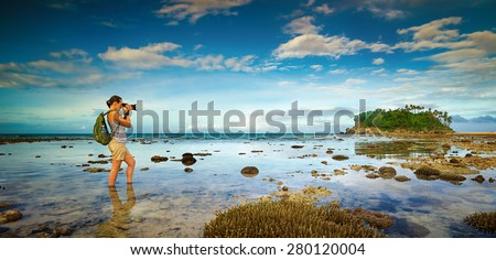 standing in the water traveler woman with backpack taking a landscape of nearby amazing island. Traveling along Asia, active lifestyle concept - stock photo