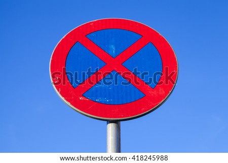 Standing is prohibited. Round road sign over blue sky background - stock photo