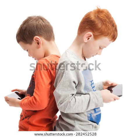 standing kids playing on mobile phones