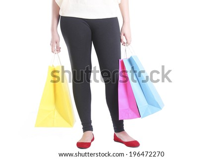 Standing lady carrying colorful shopping bags. Isolated in white background.